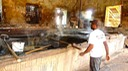 Sugarcane Juice is Ladeled by Hand from one Reducing Copper to the Nex.jpg
